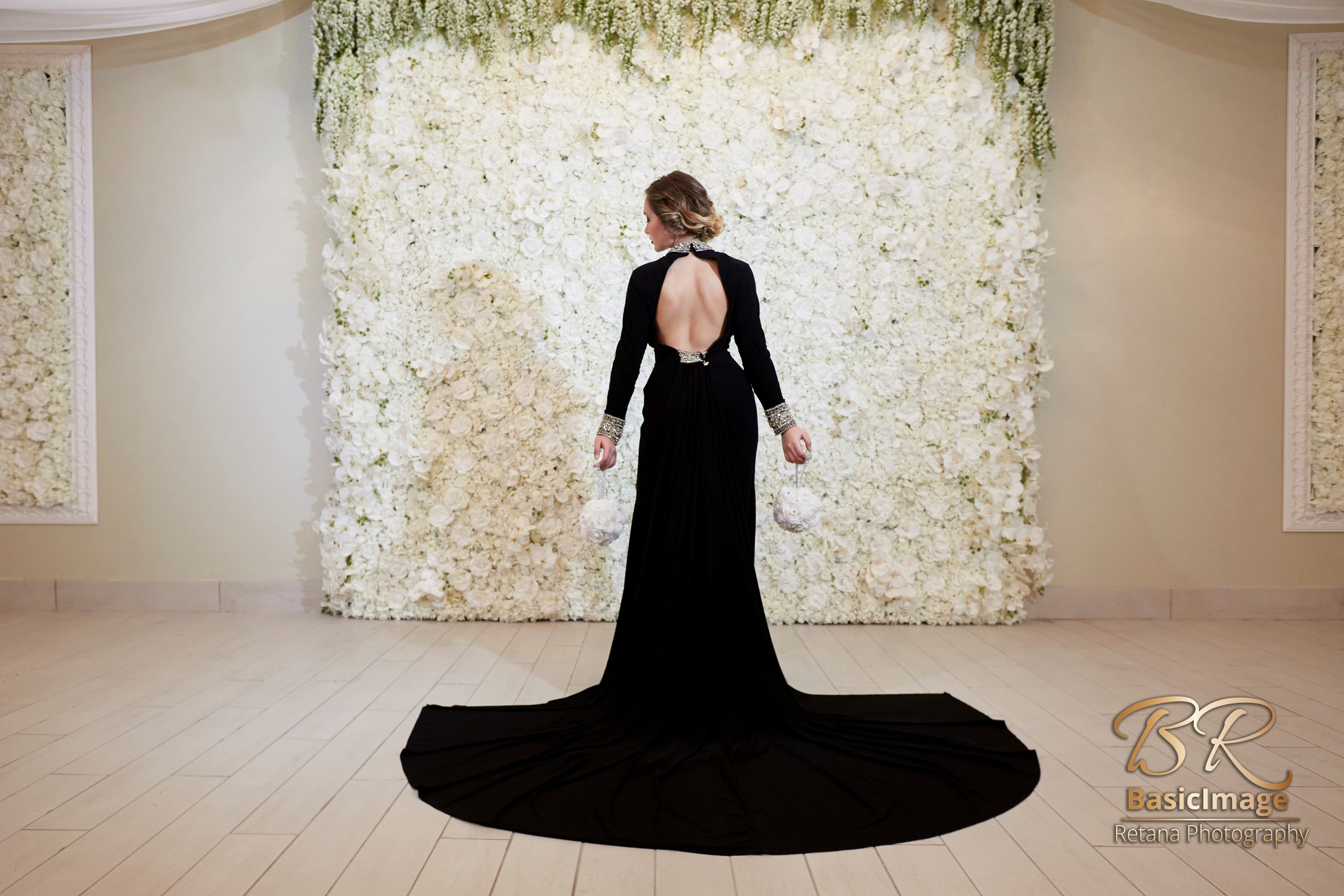 LeVenue model and wall of flowers, back turned